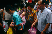 A Macanaese (Portuguese-Chinese) mother carries her baby in a sling on her back while shopping for supplies in a Macau market, China in this ex-Portuguese colony. Amid a crowded morning market, the shopping is done for families and the elderly during the rainy season.  Macau is now administered by China as a Special Economic Region (SER) and is home to a population of mainland 95% Chinese, primarily Cantonese, Fujianese as well as some Hakka, Shanghainese and overseas Chinese immigrants from Southeast Asia and elsewhere. The remainder are of Portuguese or mixed Chinese-Portuguese ancestry, the so-called Macanese, as well as several thousand Filipino and Thai nationals. The official languages are Portuguese and Chinese.