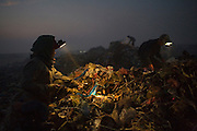 Recycling workers using headlamps at night to work in the famous Smokey Mountain Rubbish dump..RUBBISH DUMP RECYCLING. South East Asia, Cambodia, Phnom Penh. Smokey Mountain, Steung Mean Chey, is Phnom Penh's municipal rubbish dump. Thousands work there, some 600 minors and 2000 adults, recycling the city's rubbish, dumped there by garbage trucks every day. The dump is notorious as many very young children work there. People eat and sleep overnight in the rubbish and fumes, under plastic tarpaulins or in the open air. They work 24 hours a day, like miners, with headlamps at night, collecting plastic, metals, wood, cloth & paper, which they sort and clean, weigh and sell, to be carried away for recycling. A day's work typically brings less than a dollar per person. One and a half to two dollars per day per family. The overpowering, acrid odour of grey smokey fumes blows across the dump, from which the place gets its name 'Smokey Mountain'. It can be smelt miles away. The shantytowns and squats, the recycling worker's homes butt onto or are inside the dump itself. There is no running water, sanitation and many are ill. Children often work with friends or relatives. Religious and ngo's help some children, but this is often resisted by families who need the extra income they generate.///Working at night, recycling rubbish, in Smokey Mountain. The workers rent lamps and batteries for 1000 Rial (25c $ US)