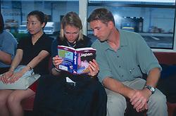 Dana & J. Nichols Researching Trip To Sendai Using Lonely Planet Guide On Train