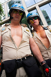 """London, June 28th 2014. Two """"motorcycle cops"""" pose for pictures as Gay Pride revellers assemble on Baker Street ahead of the parade."""