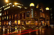 The Michelin Bibendum building at night in South Kensington. With the lights from passing vehicles registering on the film as streaks of light, we see across the road to decorative building known around London. <br /> Designed and built at the end of the Art-Nouveau period, Michelin House at 81 Fulham Road, Chelsea, London, was constructed as the first permanent UK headquarters and tyre depot for the Michelin Tyre Company Ltd. The building opened for business on 20 January 1911.