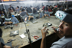 Workers make gold jewelry at Exportadores Bolivianos, a company that provides jewelry to Wal-Mart, K-mart, Bloomingdales and Macy's among others. El Alto is a largely indigenous town in Bolivia that is generally thought of as the Bolivian center  for anti-privatization and free trade sentiment, but industry benefitting from these very things are vital to El Alto.  Workers travel outside of their town, crossing road blockades on foot if necessary, to arrive to factories that can be far away. Industry and free trade is becoming more important to this politically charged town, whose protests have led to the removal of a president and foreign water company lately. Without the presence of private companies El Alto would be even more impoverished than it already is, bringing to a head the towns presumed nationalistic identity and its very real reliance on private industry.