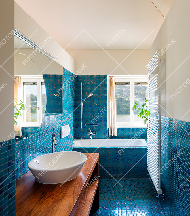 Modern blue bathroom interior, overlooking nature. No one inside is very empty. Warm light