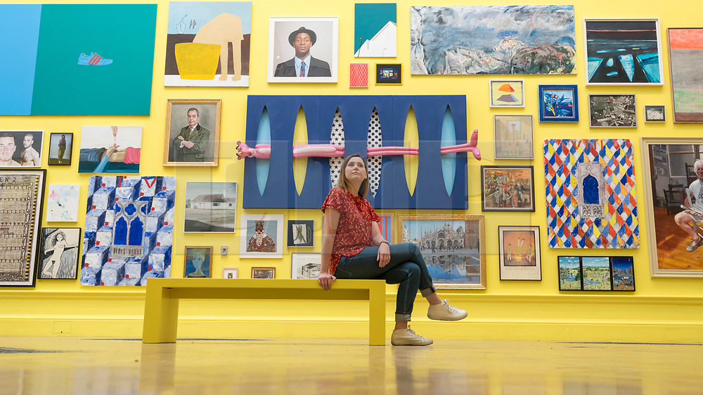 © Licensed to London News Pictures. 05/06/2018. LONDON, UK. A staff member sits amidst artworks in a vividly painted gallery at a preview of the 250th Summer Exhibition at the Royal Academy of Arts in Piccadilly, which has been co-ordinated by Grayson Perry RA this year.  Running concurrently, is The Great Spectacle, featuring highlights from the past 250 years.  Both shows run 12 June to 19 August 2018.  Photo credit: Stephen Chung/LNP
