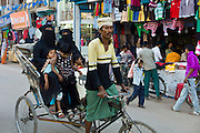 Street scene in holy city of Varanasi, young muslim women in black burkhas ride with their children in rickshaw, Benares, Northern India