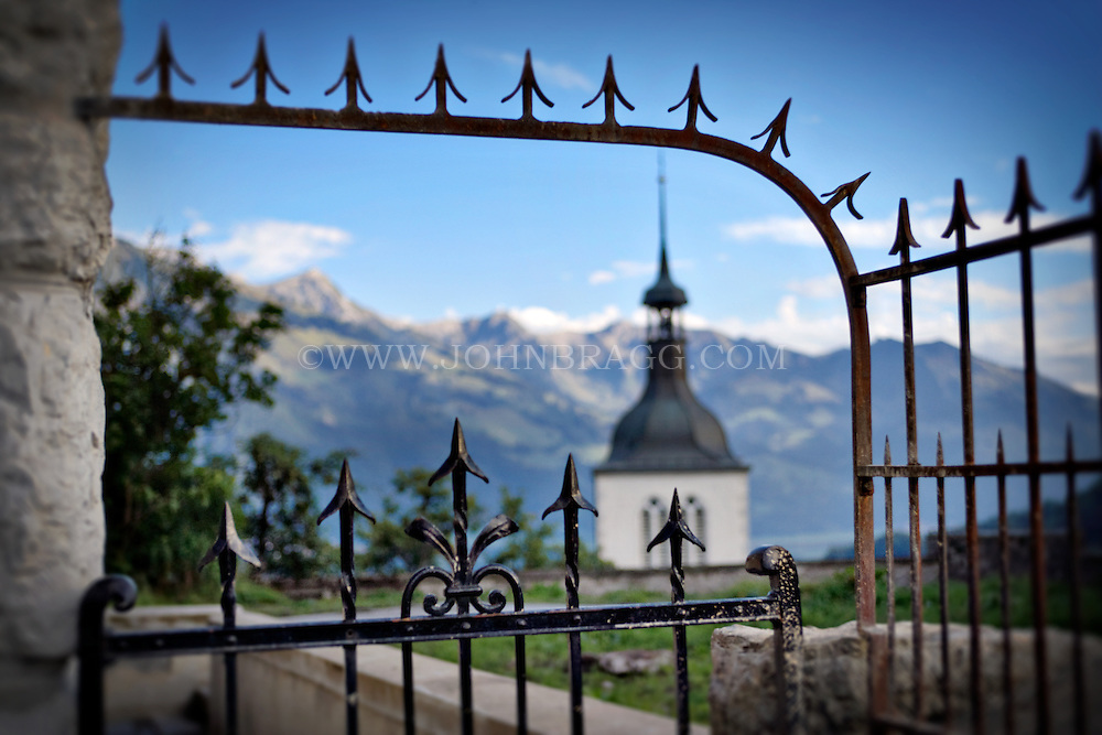 Old Fence outside of the Church of Gruyere, Switzerland with a view of the alps in the background