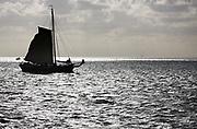 A ship is raising its sails on the Waddenzee outside the harbour of Lauwersoog //  Zonlicht schijnt op het water van de Waddenzee. Een schip hijst buiten de haven van Lauwersoog de zeilen.