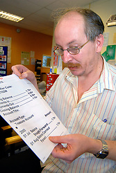 Man with learning disabilities reading large print bank statement; community centre; Bradford; Yorkshire UK