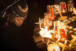 "© Licensed to London News Pictures . 01/12/2013 . Manchester , UK . A boy kneels beside candles placed by visitors to the park . World AIDS Day commemoration in Sackville Park , Manchester , this evening (Sunday 1st December 2013) including a candle-lit procession around the city's "" Gay Village "" . Photo credit : Joel Goodman/LNP"