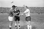 24/05/1964<br /> 05/24/1964<br /> 24 May 1964<br /> Soccer International: Ireland v England at Dalymount Park, Dublin. England won the game 3-1.  Irish captain, Noel Cantwell (left) and English captain Bobby Moore shake hands and exchange plaques prior to the match with referee Robert Holley Davidson (Scotland) looking on.