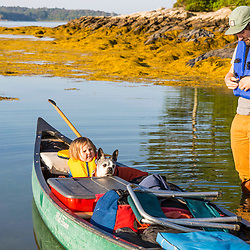 A couple and their young daughter (and dog) canoeing after a night of camping on Lanes Island in Casco Bay. Yarmouth, Maine.