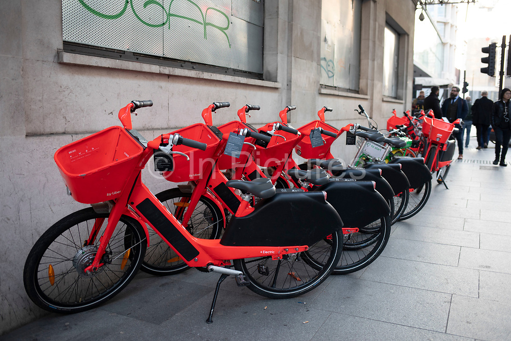 Row of standing Jump dockless bike sharing electric cycles on 21st January 2020 in London, England, United Kingdom. Social Bicycles Inc., doing business as Jump, is a dockless scooter and electric bicycle sharing system operating in the United States, Germany, Portugal and the United Kingdom. The bikes are a bright red orange. They can be located using the Jump or Uber apps, and users are charged to their Uber account.