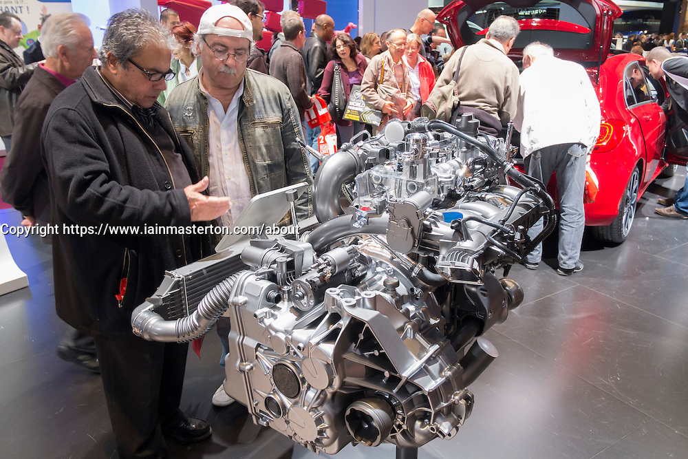 Visitors look at new petrol engine by Mercedes benz at Paris Motor Show 2012