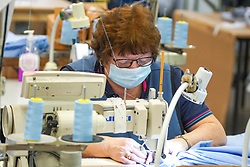 © Licensed to London News Pictures. 21/04/2020. Dukinfield, UK.  A woman wearing a face mask  sews medical clothing as staff at Tibard begin working around the clock on an order of 5,000 units of nurses  uniforms (scrubs) for NHS workers per week in Dukinfield , owing to growing demand during the COVID-19 pandemic. The factory typically manufactures uniforms for the catering industry.  Photo credit: Ioannis Alexopoulos /LNP