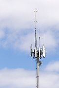 3 sector cellular telecom communications panel antenna array for the mobile telephone system on a cellsite pole tower with two-way radio antennas. <br />