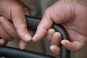 extreme close up of hands holding a suitcase on wheels
