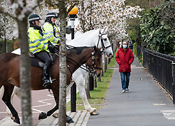 © Licensed to London News Pictures. 30/03/2020. London, UK. A man wearing a medical face mask walks near police patrolling on horseback through Regents Park in London. Members of the public have been told they can only leave their homes when absolutely essential, in an attempt to fight the spread of COVID-19, . Photo credit: Ben Cawthra/LNP