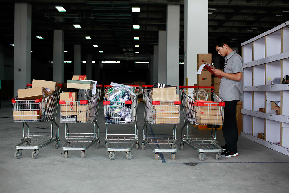 """A warehouse employee work to fill an oders at the Yihaodian warehouse and logistics center in Shanghai, China on 23 August, 2011. As online supermarkets is attracting a rapidly increasing number of young consumers, especially women, U.S. giant Walmart has acquired a minority stake in Yihaodian, or """"The Store"""", a young but very successful E-Commerce company that sells and delivers everything from food, daily household  items, electronics, and clothing."""