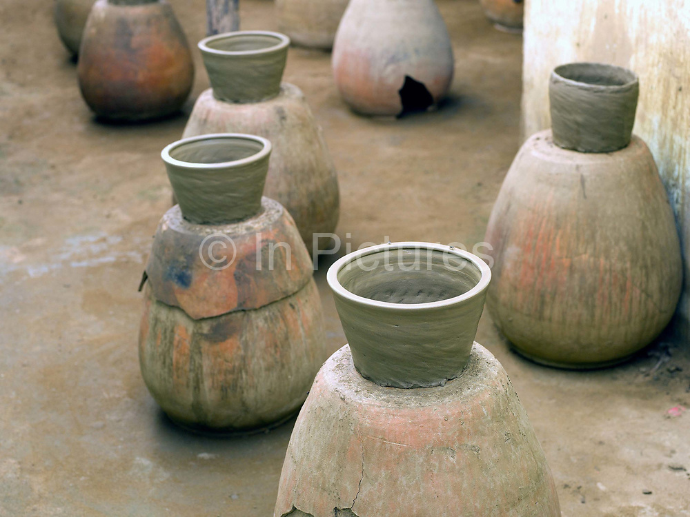 Hand-making ceramic pots using a traditional method in the famous pottery village of Bau Truc in Central Vietnam. Cham potters do not use a wheel to make pots, instead clay is pressed into shape using the hands. Layers of clay are added to the original piece and the potter moves around the object, pressing the clay into the desired shape. They are then put directly in the sun and completely bone dried, making them ready to be fired. Firing is done in an open pit with temperatures going up to 800 degree Celcius. The pots are arranged together and covered with layers of rice straw, which is set on fire.