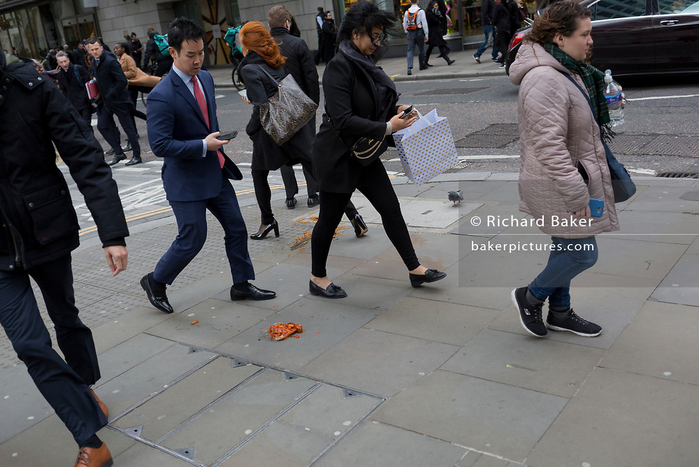 Pedestrians avoid a noodle and sauce takeaway, dropped and discarded on the pavement during lunch-hour in the capital's financial district, on 4th February 2020, in the City of London, England.