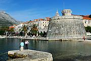 Small (Mala Knezeva Kula) and Large (Velika Knezeva Kula) Prince's or Governor's towers, two children on stone jetty in foreground. Korcula old town, island of Korcula, Croatia.