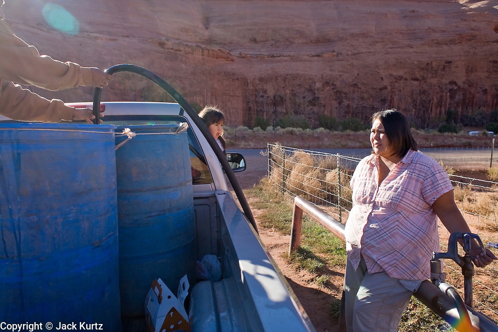 22 OCTOBER 2007 -- MONUMENT VALLEY, UT: ORLANDO CLY and his wife, MARIE CLY, Navajo Indians living on the Navajo Reservation in northern Arizona, fill 50 gallon barrels with potable water at the well at Goulding's Trading Post near Monument Valley, UT. The well at Goulding's was first dug by Seventh Day Adventists missionaries and is the only source of clean, free water for miles around. More than 30 percent of the homes on the Navajo Nation, about the size of West Virginia and the largest Indian reservation in the US, don't have indoor plumbing or a regular supply of domestic water. Many of these homes have to either buy water from commercial vendors or haul water from public wells. A Federal study showed that the total cost of hauling water was about $113 per 1,000 gallons. A Phoenix household, in comparison, pays just $5 a month for up to 7,400 gallons of water. The lack of water on the reservation means the Navajo are among the most miserly users of water in the United States. Families that have to buy or haul water use only about 15 gallons of water per day per person. In Phoenix, by comparison, the average water use is about 170 gallons per day.  Photo by Jack Kurtz/ZUMA Press