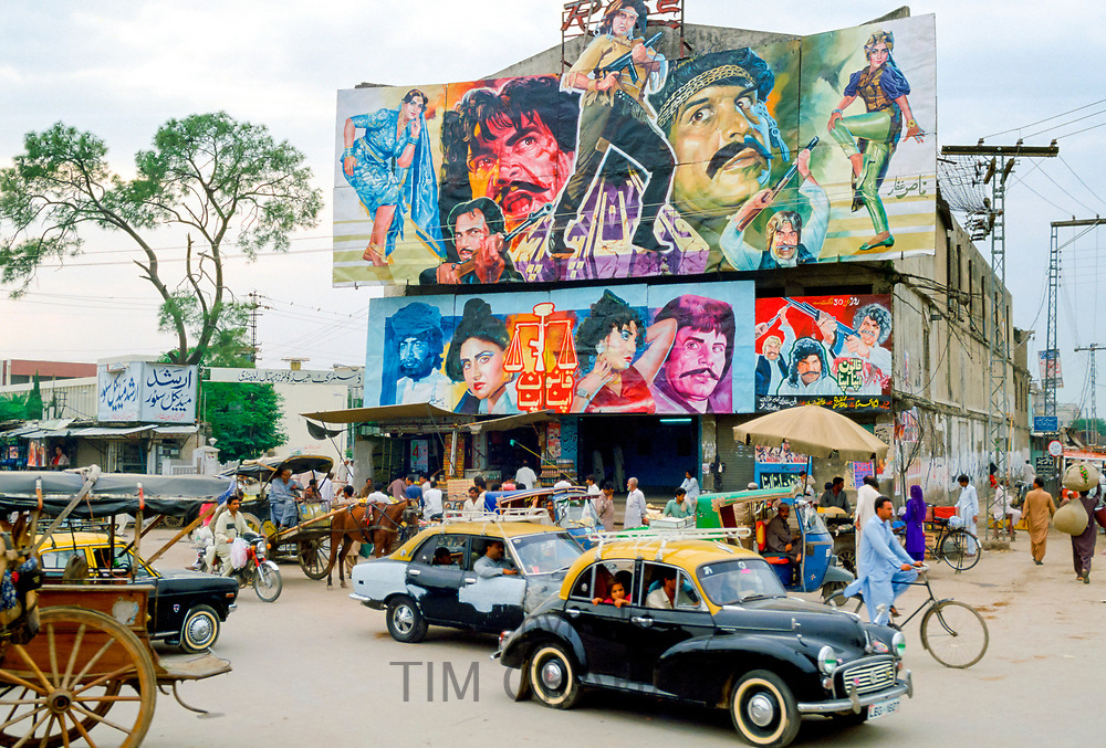 """Street scene in Islamabad, Pakistan showing rickshaws, an old two-tone Morris Minor car and the local cinema advertising films often described as """"Bollywood'."""