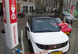 Electric cars being recharged at public recharging point on street in Amsterdam The Netherlands