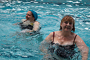 Local people join in an excercise class at the Cally Pool swimming pool in London. This group consists of people joining the class for various reasons including weight loss and general fitness.