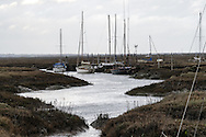 Boats lie moored in a creek at Tollesbury, England