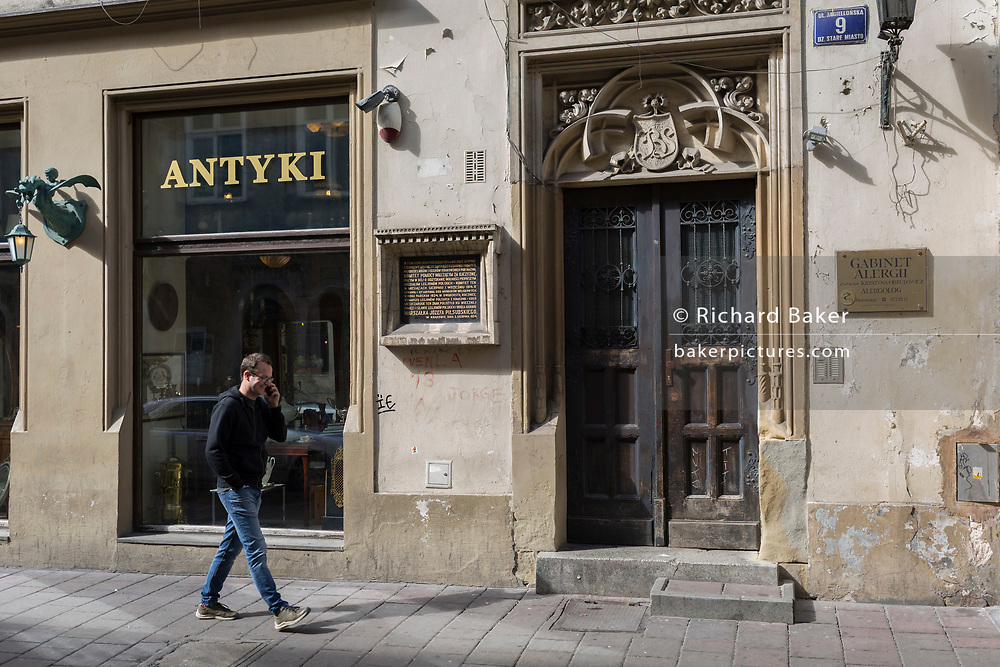 A man walks past old doorway architecture in central Krakow, on 23rd September 2019, in Krakow, Malopolska, Poland.