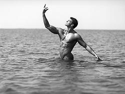 naked bodybuilder in the ocean