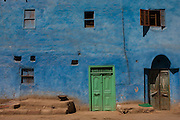 Local architecture of a green door and blue painted house in in a village near Medinet Habu on the West Bank of Luxor, Nile Valley, Egypt.