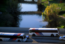 Two Metro buses passing each other on a bridge over Buffalo Bayou