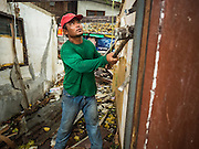 28 SEPTEMBER 2015 - BANGKOK, THAILAND: A demolition worker uses a sledge hammer to tear down a home at Wat Kalayanamit. Fifty-four homes around Wat Kalayanamit, a historic Buddhist temple on the Chao Phraya River in the Thonburi section of Bangkok, are being razed and the residents evicted to make way for new development at the temple. The abbot of the temple said he was evicting the residents, who have lived on the temple grounds for generations, because their homes are unsafe and because he wants to improve the temple grounds. The evictions are a part of a Bangkok trend, especially along the Chao Phraya River and BTS light rail lines. Low income people are being evicted from their long time homes to make way for urban renewal.   PHOTO BY JACK KURTZ
