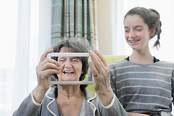 Senior woman with granddaughter taking photos using digital tablet at rest home