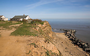Cliff top buildings at risk of coastal erosion, Happisburgh, Norfolk, England with beach rock armour defences