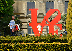 © Licensed to London News Pictures. 24/05/2012. Waddesdon, UK. A woman walks past a sculpture by Robert Indinana. People enjoy the warm weather amongst an exhibition of contemporary sculpture at Waddesdon Manor, Buckinghamshire, today 24th May 2012. The exhibition is being held by Christie's as part of a private sale. Photo credit : Stephen Simpson/LNP
