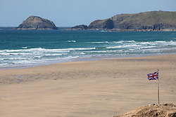 """© Licensed to London News Pictures. 11/05/2020. Perranporth, UK. Perranporth beach, on the North coast of Cornwall is nearly empty, the day after British Prime Minister Boris Johnson announced a 'road map' to lift lockdown restrictions due to Covid-19, (Coronavirus). A rise in """"staycations"""" - the concept of holidaying in your home country rather than travelling abroad - is expected, with many visitors planning to visit Cornwall. However, an ongoing campaign titled """"#ComeBackLater"""" is trying to persuade tourists not to visit the county until it is safe to do so. Photo credit : Tom Nicholson/LNP"""