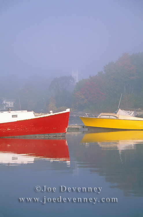 Red and yellow boats tied to the dock in the Damariscotta River. Damariscotta, Maine