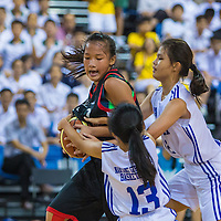 Carissa Chan (#7) of Anglican High protects the ball against Tan Qi Qing (#12) and (#13) of Nanyang Girls' High during the final of the National 'C' Division Basketball Championship at the OCBC Arena at the Singapore Sports Hub on August 28, 2014, in Singapore.