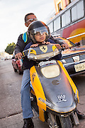 A young boy on his fathers motorcycle in Oaxaca, Mexico.
