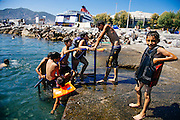 Refugees enjoy swimming at the port of Mytilini while they wait for a ferry to Athens in Lesvos, Greece on Aug 18th, 2015.