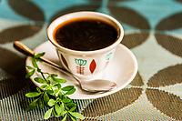 Ethiopian coffee served with a tena adam leaf (a spice), Kanta Lodge, Konso, Ethiopia.