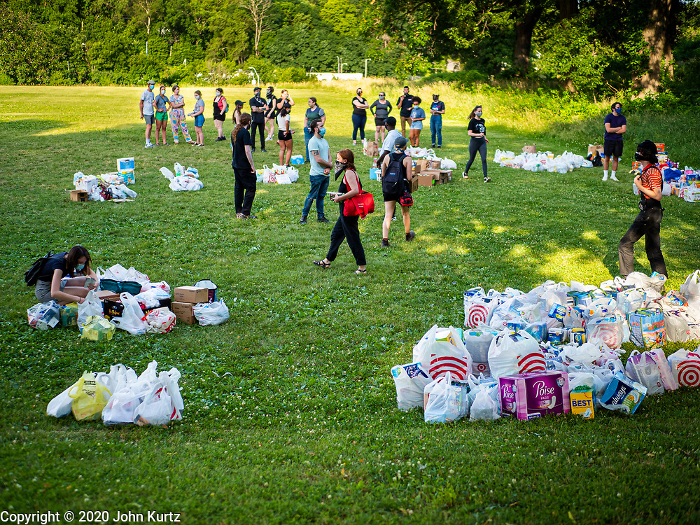 25 JUNE 2020 - DES MOINES, IOWA: Supporters of Black Lives Matter walk among supplies for the homeless donated to BLM. Nearly 100 volunteers came to a community support event organized by Black Lives Matter in Good Park in Des Moines. They sorted supplies donated to BLM, including food, sanitary supplies, first aid supplies, batteries, blankets, tents, and bottled water. The emergency packages will be distributed to homeless people in Des Moines.          PHOTO BY JACK KURTZ