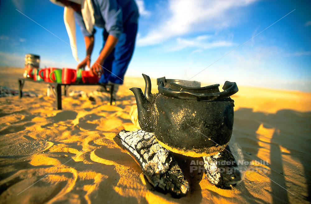 Egypt, 2000 - Desert trek camp site. Tea water boils on a tiny fire as a trekker in background prepares cups.