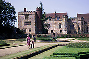 Man and woman standing in gardens of Penshurst Place and castle, Kent, England in 1970