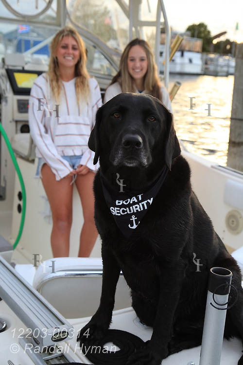Carina Whitlow and a friend Keagan Fischer laugh as her dog Gunner keeps guard aboard her boat in marina at Alpena, Michigan.
