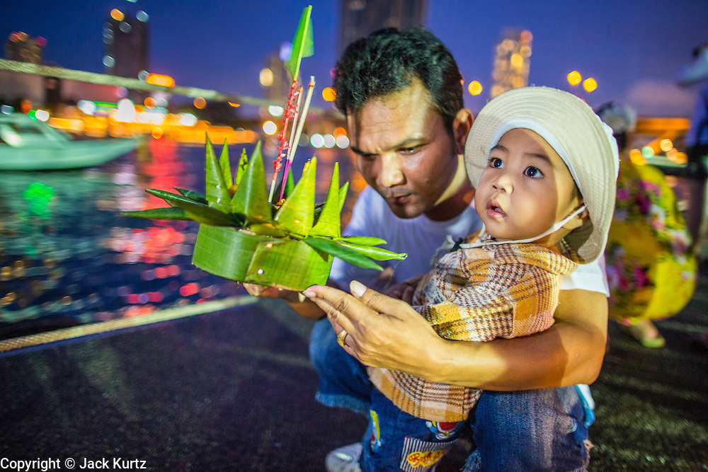 28 NOVEMBER 2012 - BANGKOK, THAILAND:  A man helps his son launch their krathong during Loy Krathong at Wat Yannawa in Bangkok. Loy Krathong takes place on the evening of the full moon of the 12th month in the traditional Thai lunar calendar. In the western calendar this usually falls in November. Loy means 'to float', while krathong refers to the usually lotus-shaped container which floats on the water. Traditional krathongs are made of the layers of the trunk of a banana tree or a spider lily plant. Now, many people use krathongs of baked bread which disintegrate in the water and feed the fish. A krathong is decorated with elaborately folded banana leaves, incense sticks, and a candle. A small coin is sometimes included as an offering to the river spirits. On the night of the full moon, Thais launch their krathong on a river, canal or a pond, making a wish as they do so.   PHOTO BY JACK KURTZ