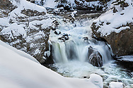 Firehole Falls in Yellowstone National Park decorated with a blanket of snow. Winter is a tough time to visit Yellowstone but the extra expense is worth the reward.